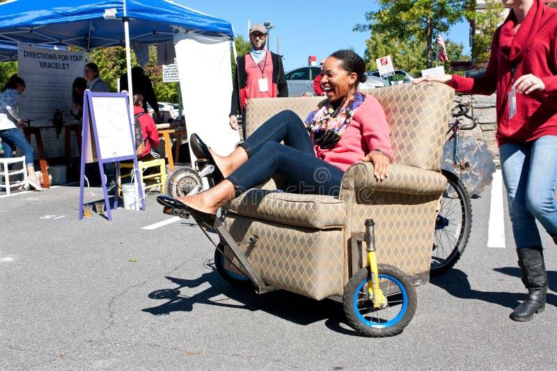 妇女操纵穿着或行为古怪的人在轮子的家具片断在独特的市场 库存图片