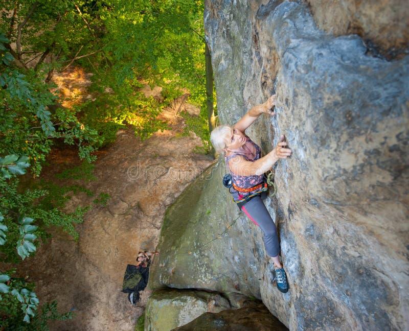 妇女攀岩运动员在岩石墙壁上上升 免版税图库摄影