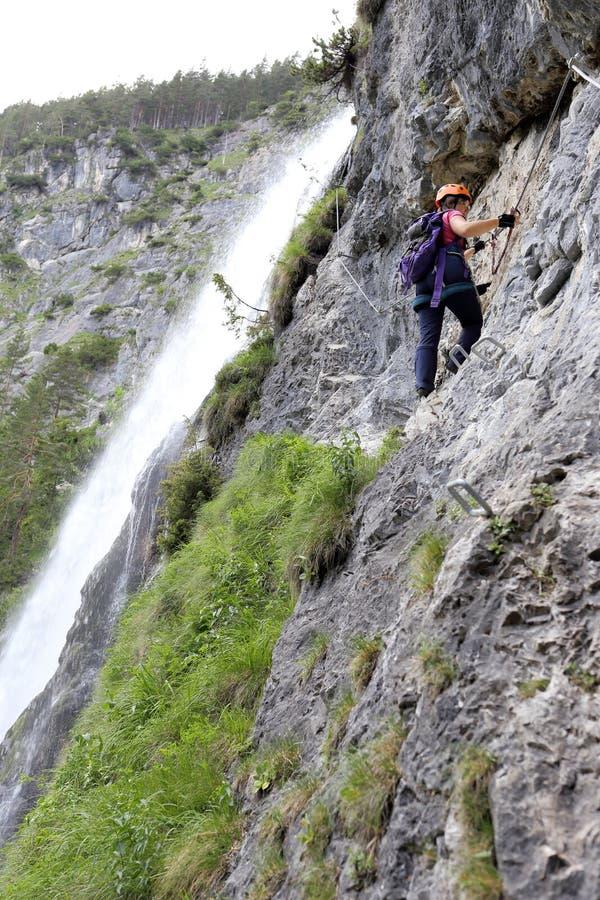 妇女攀登岩石墙壁 免版税图库摄影