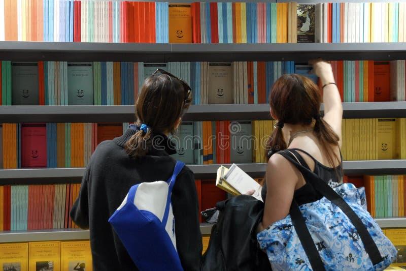 妇女支持看法从架子的采摘书在书市 库存照片