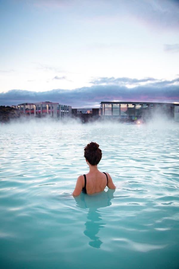 妇女放松并且享用温泉在冰的温泉蓝色盐水湖 免版税库存图片
