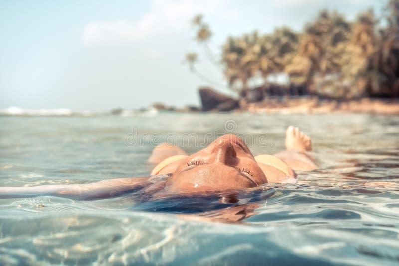 妇女放松的和晒日光浴的思考在平静的海海滩棕榈树移动热带假期生活方式 库存照片