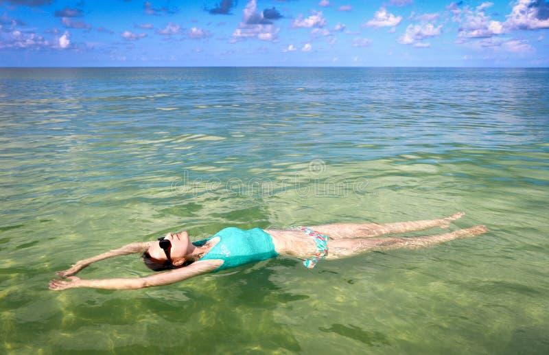 妇女放松的漂浮在海洋 库存照片