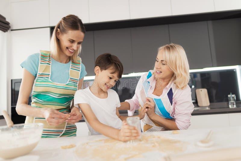 妇女教她的儿子烹调自创蛋糕 她的母亲帮助她 男孩做圈子与玻璃的面团 图库摄影
