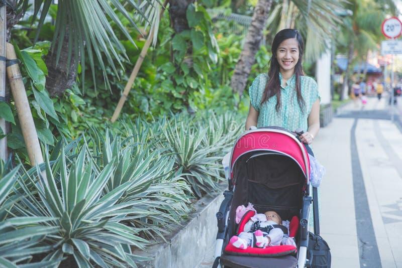 Download 妇女散步与她的在婴儿车里面的婴孩 库存图片. 图片 包括有 漫步, 边路, 孩子, 放松, 胡同, 婴孩 - 62530005