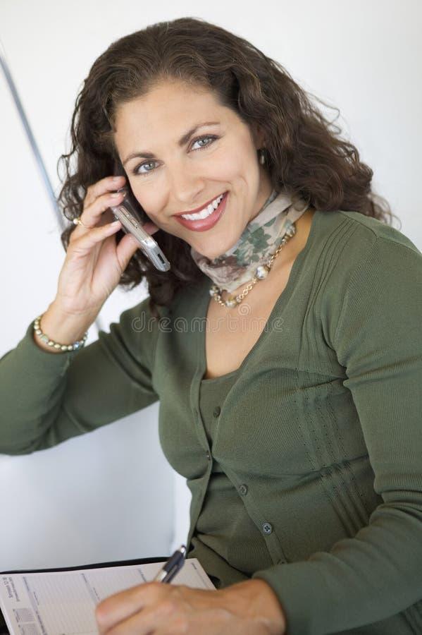 妇女文字和使用手机画象 免版税库存图片