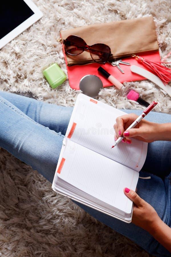妇女文字的特写镜头到她的书桌日志里 库存图片
