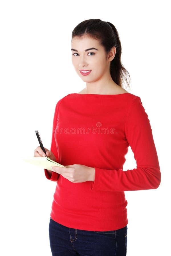 妇女文字笔记和计划她的日程表 库存图片