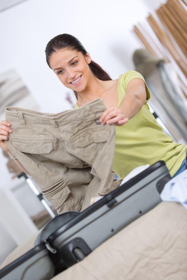 妇女新的旅途的包装行李 免版税库存图片
