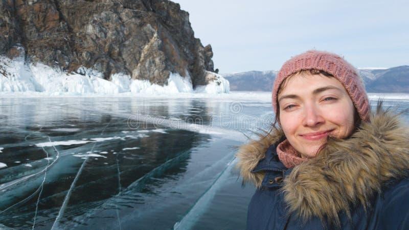 妇女旅客做一selfie反对岩石和贝加尔湖冰 冬季衣服的微笑的旅客 免版税库存照片