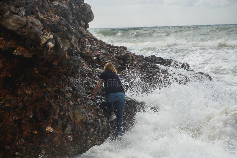 妇女旅游上升在风雨如磐的海的岩石有大波浪的,飞溅和泡沫 绝望和危险行动 免版税库存图片