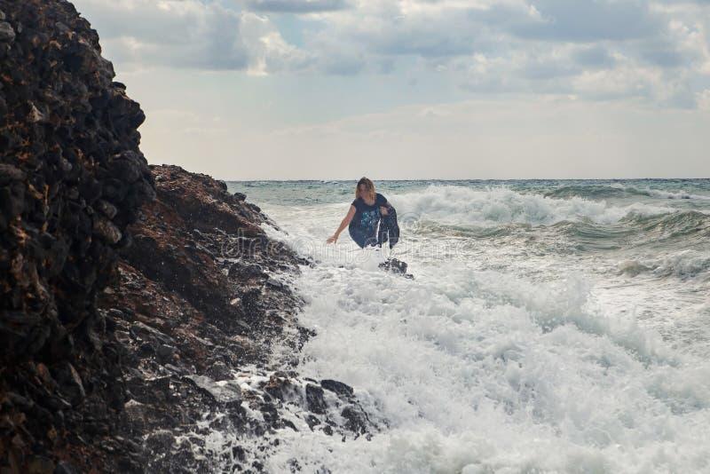 妇女旅游上升在风雨如磐的海的岩石有大波浪的,飞溅和泡沫 绝望和危险行动 免版税库存照片