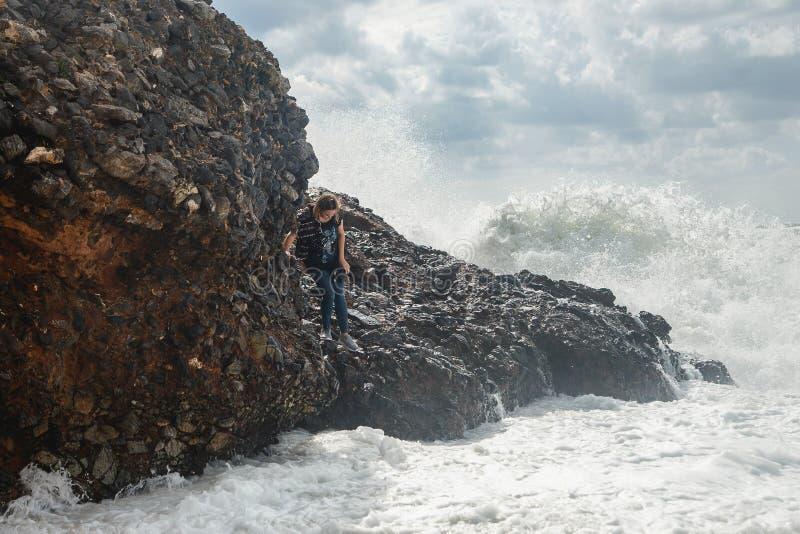 妇女旅游上升在风雨如磐的海的岩石有大波浪的,飞溅和泡沫 绝望和危险行动 库存照片
