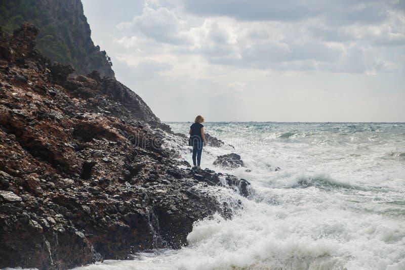 妇女旅游上升在风雨如磐的海的岩石有大波浪的,飞溅和泡沫 绝望和危险行动 库存图片