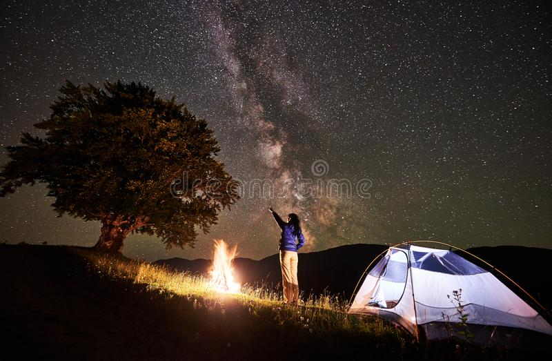 妇女旅游休息在野营在满天星斗的天空和银河下的晚上 免版税库存图片