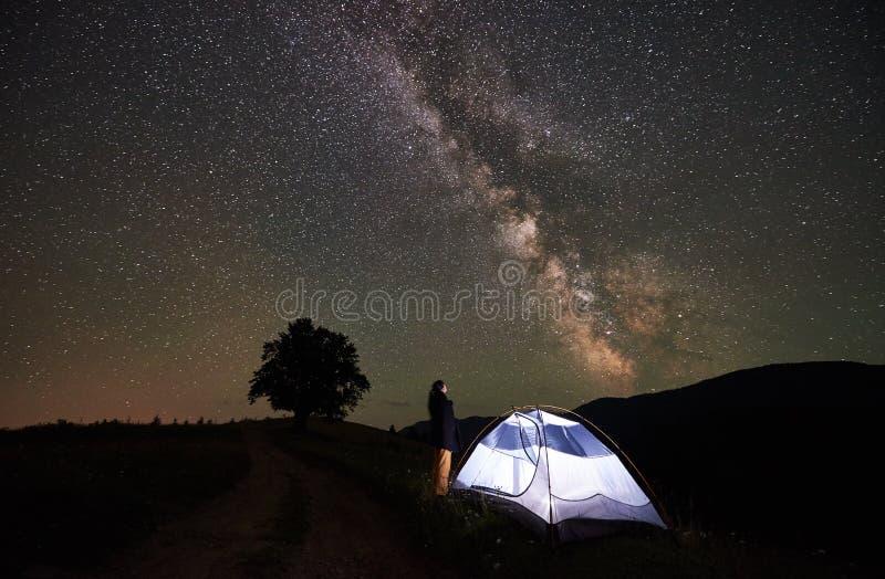 妇女旅游休息在野营在满天星斗的天空和银河下的晚上 库存图片