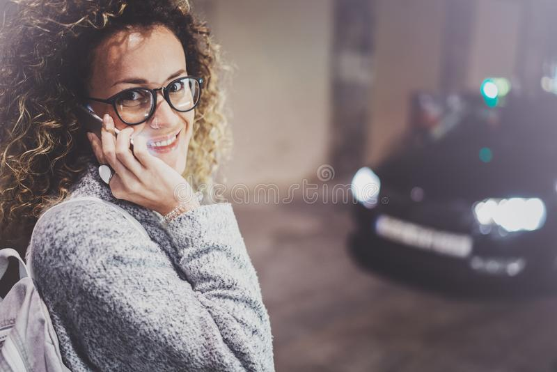 妇女旅游佩带的眼睛玻璃叫出租汽车服务用手机,当在街道上站立在夜时 免版税库存图片