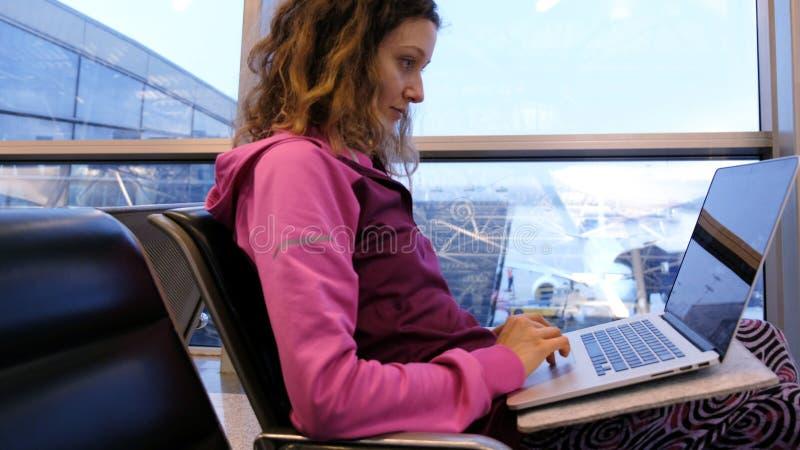 妇女旅游自由职业者打开膝上型计算机,并且印刷品,在机场等待飞机和飞行,在候诊室 免版税图库摄影