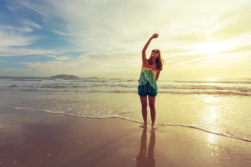 妇女旅行享用采取在海滩的一照片selfie与日出 免版税库存照片