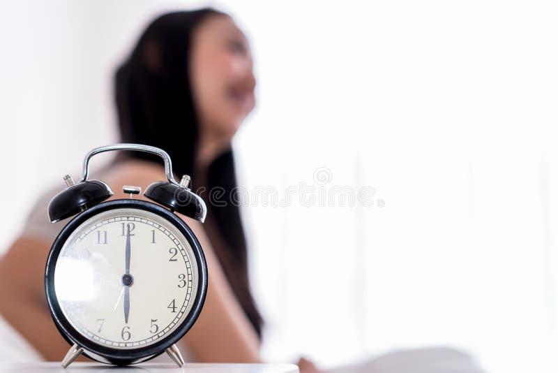 妇女早早醒了当在六的闹钟展示 库存图片