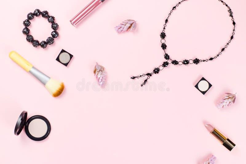 妇女时装配件、首饰和化妆用品在桃红色背景 平的位置 免版税库存图片