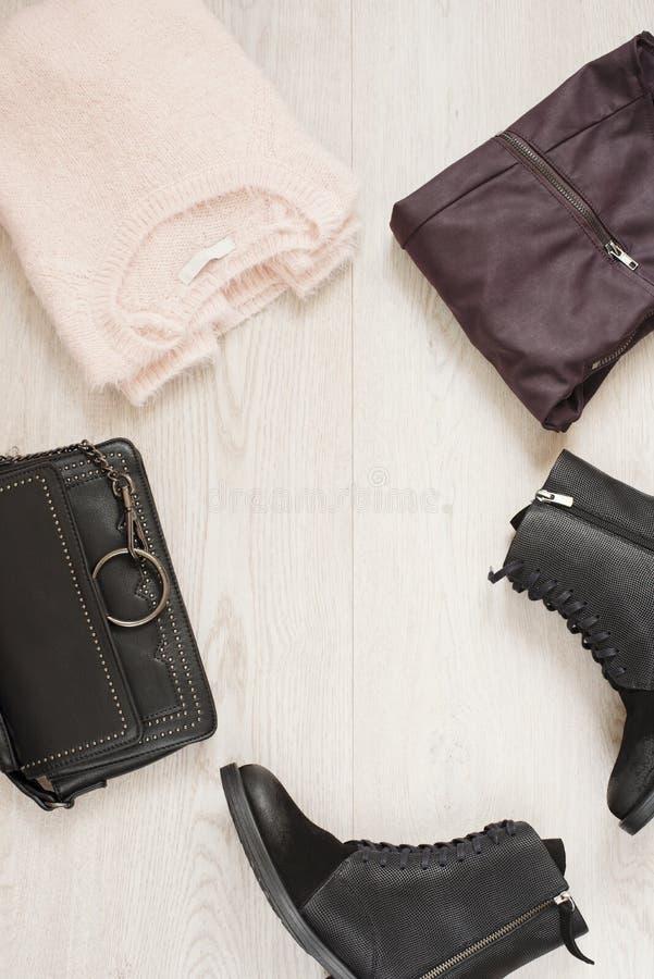 妇女时髦时尚给与毛线衣、皮革裤子、军事起动和袋子的拼贴画穿衣 平的位置 免版税图库摄影