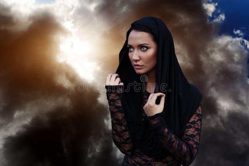 妇女是一位先知巫师和一位传教者一个黑神秘的斗篷的有敞篷的反对剧烈的背景 免版税库存照片