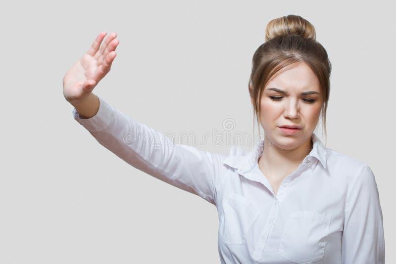 妇女是令人厌恶的 一件白色衬衣的一名妇女 库存图片