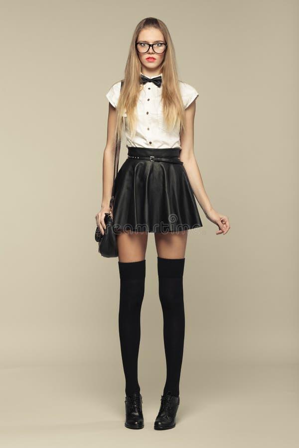 妇女是在黑微型裙子的时尚样式 库存图片