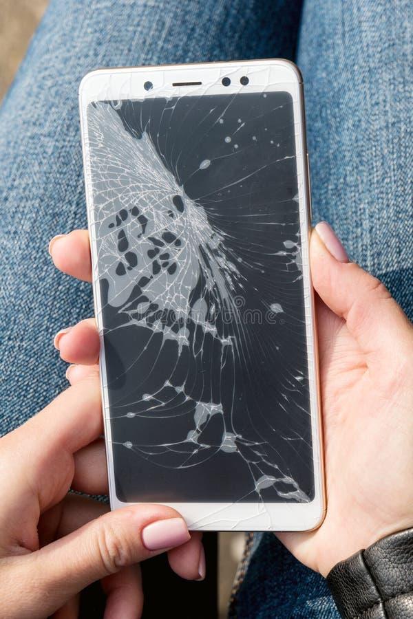妇女是坐和拿着有一个破裂的屏幕的一个残破的巧妙的电话 库存图片