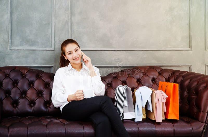 妇女是工作和愉快的 美丽的亚裔妇女微笑着 亚裔妇女与在沙发的灰色膝上型计算机一起使用在平均观测距离的屋子里 免版税图库摄影