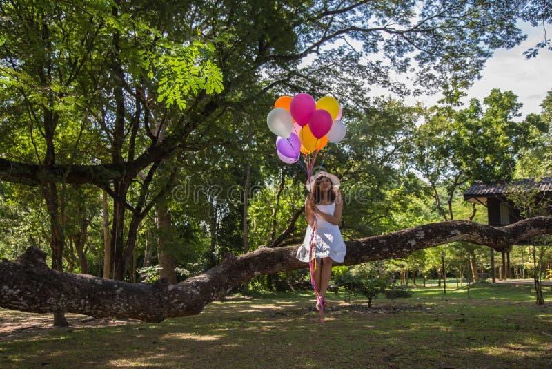 妇女是微笑,坐拿着一个透明球在树下 免版税库存图片