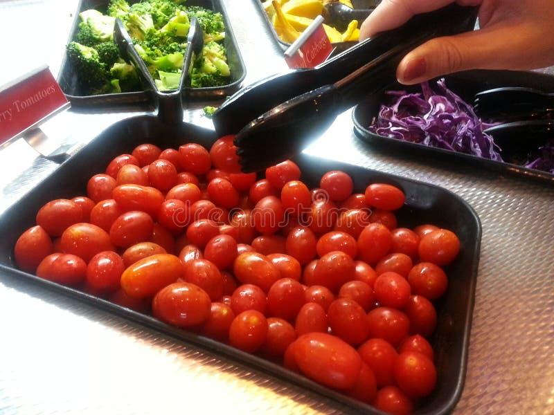 妇女是拾起从菜沙拉柜台的一个蕃茄在餐馆 图库摄影