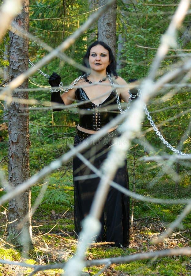 妇女是黑被囚禁的一个巫婆在树之间在一个密集的森林万圣夜里 免版税库存照片