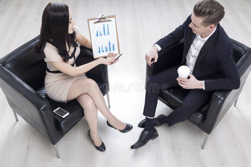 妇女显示一张图表给她的同事 免版税库存图片