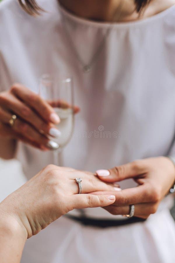 妇女显示她的朋友一个婚戒,华美的修指甲白色礼服关闭  免版税库存图片