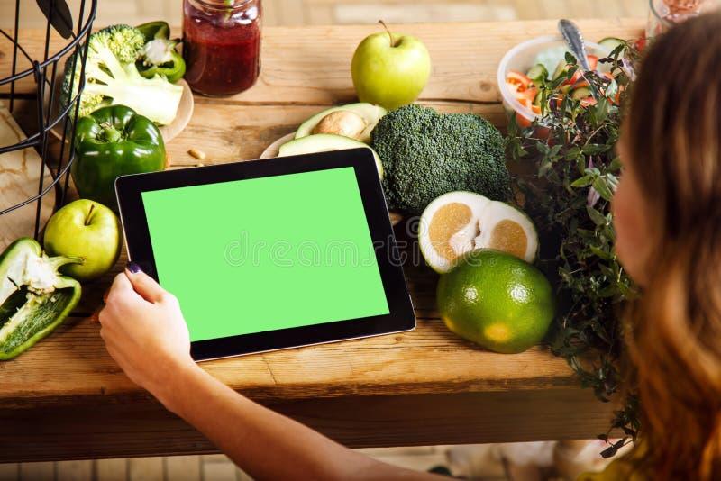 妇女显示片剂在厨房用桌上 免版税图库摄影