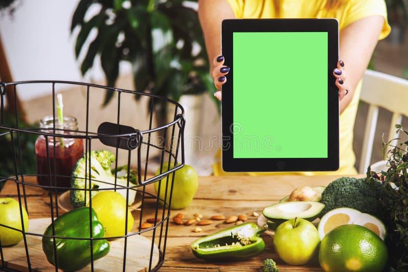 妇女显示片剂在厨房用桌上 库存照片