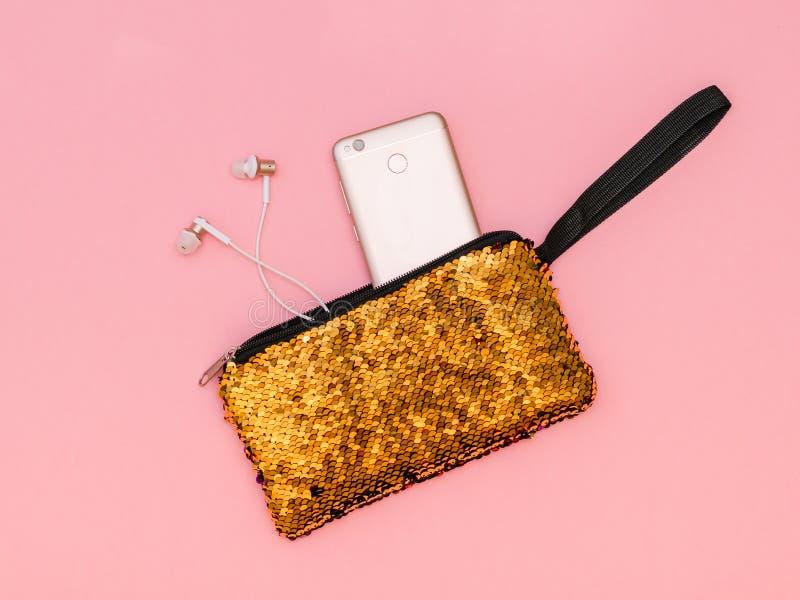 妇女有一个黏附的金子颜色电话和耳机的` s提包在一张桃红色桌上的 淡色 平的位置 免版税图库摄影