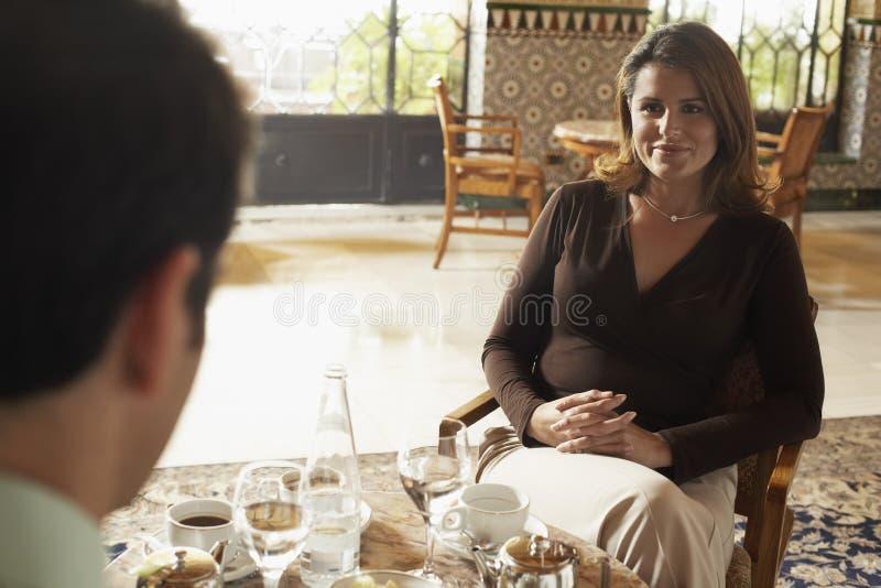 妇女有与人的膳食在餐馆 库存照片