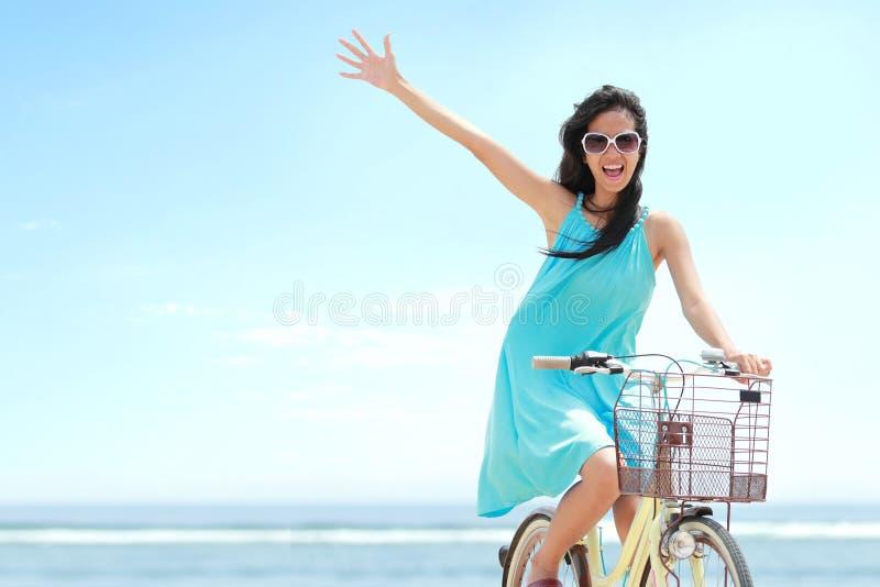 妇女有乐趣骑马自行车在海滩 库存照片