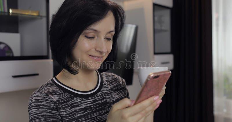 妇女有在社会媒介的闲谈使用享受聊天的智能手机对朋友 库存照片