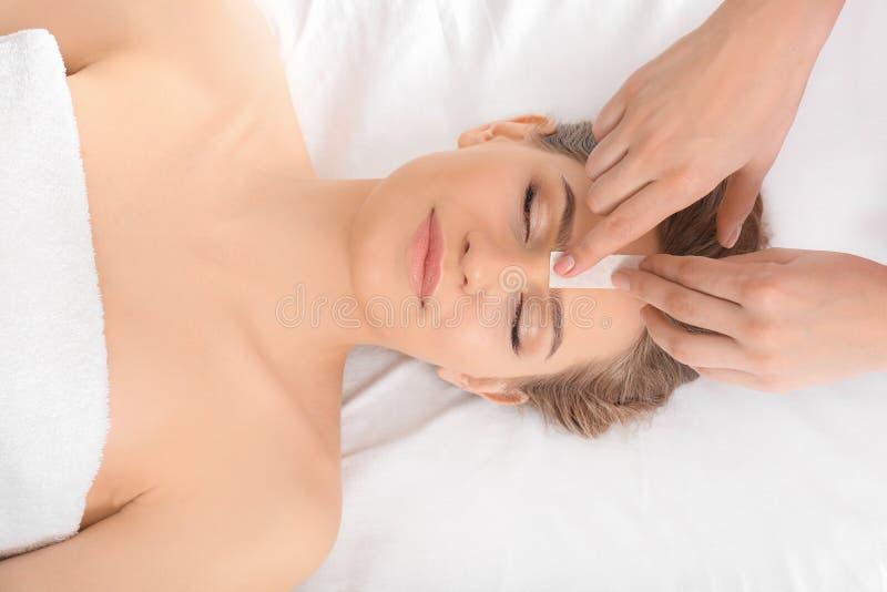 妇女有头发在面孔的移动程序与蜡在沙龙 免版税库存照片
