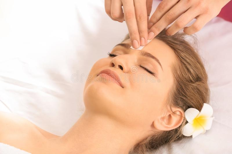 妇女有头发在面孔的移动程序与蜡在沙龙 图库摄影