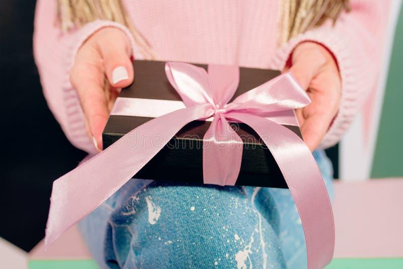 妇女有拿着黑当前箱子的桃红色修指甲的` s手 库存照片