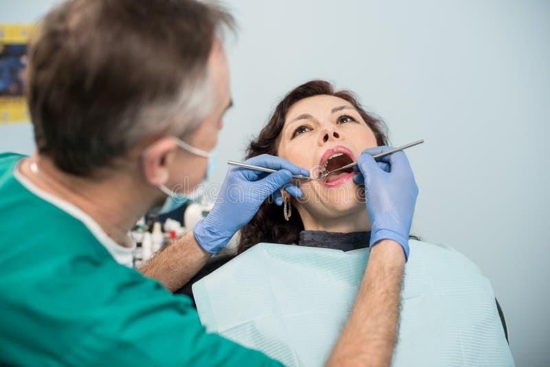 妇女有牙齿检查在牙齿办公室 牙医有牙齿工具的审查的患者` s牙 库存图片