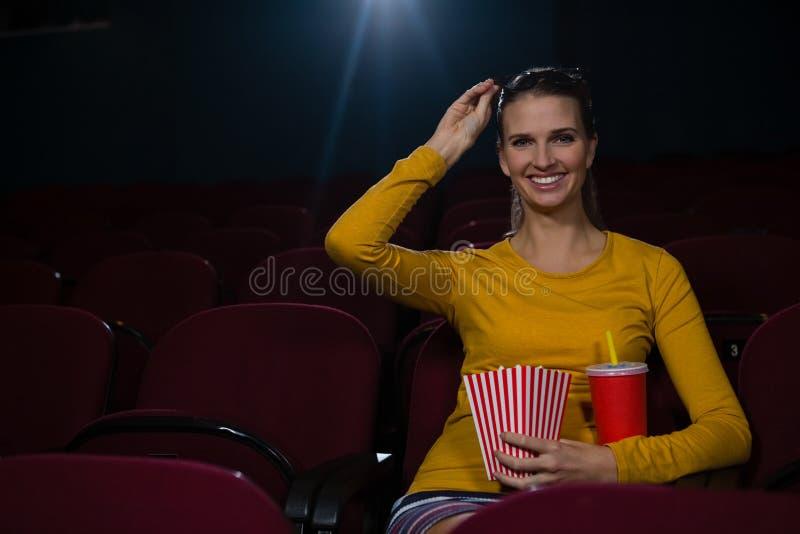 妇女有玉米花和饮料,当观看电影在剧院时 免版税库存照片