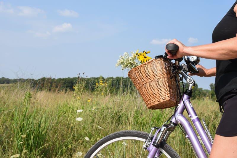 妇女有篮子的骑马自行车有很多花 免版税图库摄影