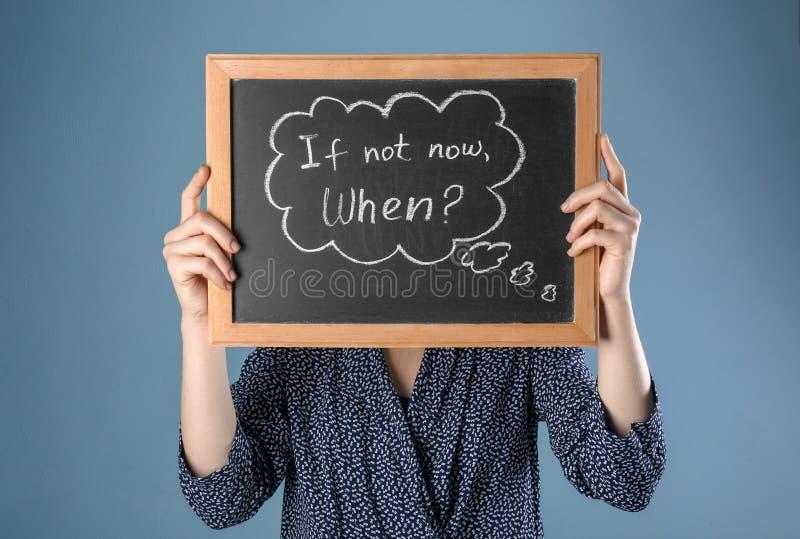 妇女有词组的藏品黑板,如果不现在 什么时候?在颜色背景 E 免版税库存图片