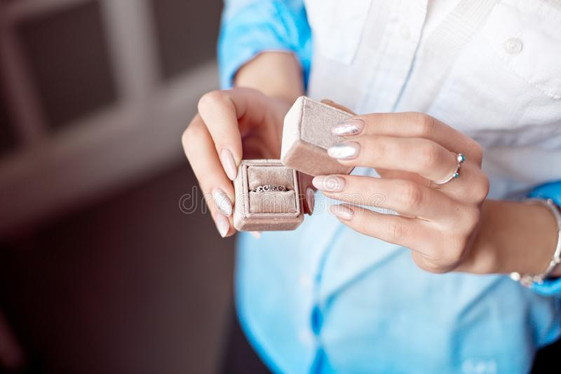 -妇女有豪华圆环的在窗口背景,特写镜头藏品箱子 免版税库存图片